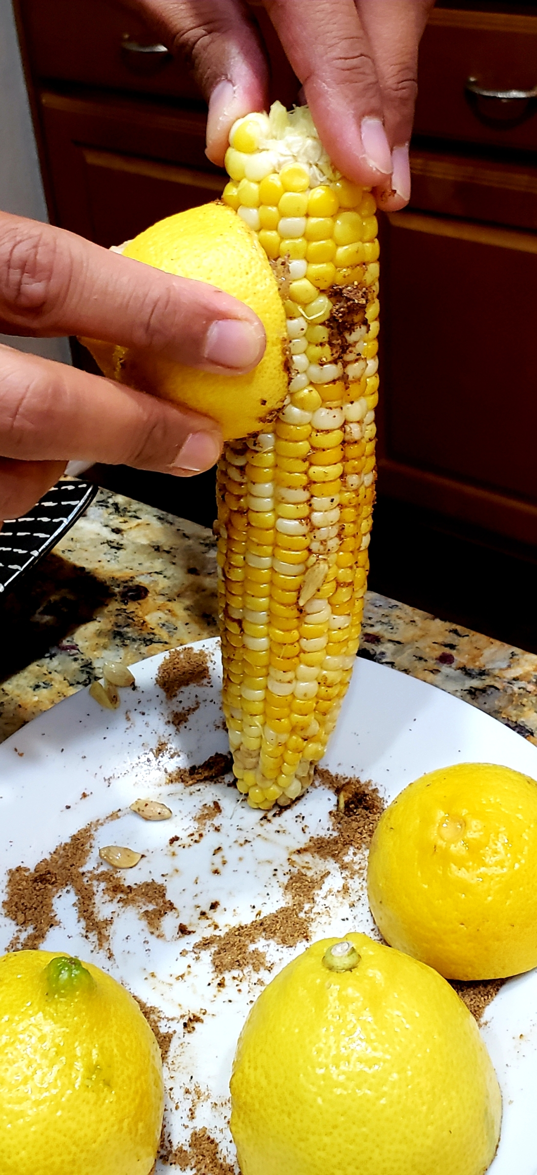 Rubbing the spiced lemon onto the corn